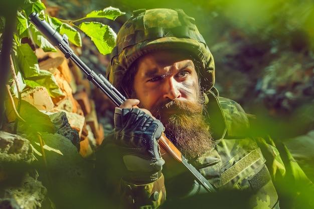 Żołnierz o smutnej twarzy w wojskowym hełmie i kamuflażu