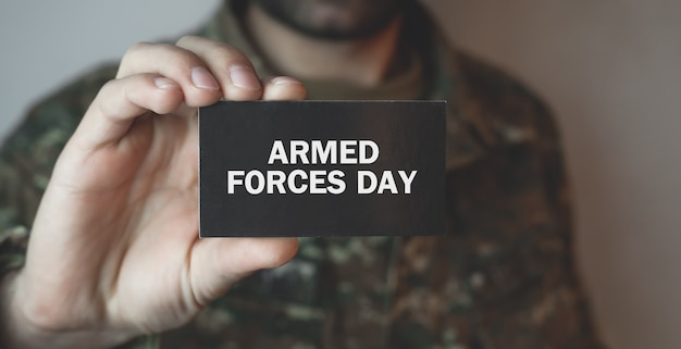 Żołnierz pokazuje tekst dzień sił zbrojnych.
