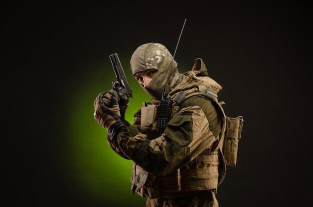 Żołnierz-sabotażysta w wojskowym stroju z bronią na ciemnej ścianie