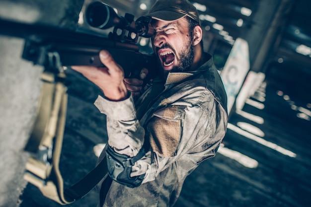 Żołnierz się śmieje. patrzy przez obiektyw, ponieważ celuje. facet ma ochotę strzelać z karabinu.