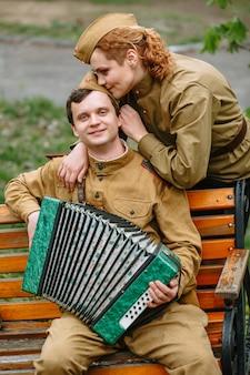 Żołnierz siedzi na ławce, grając na akordeonie i kobiecym żołnierzu