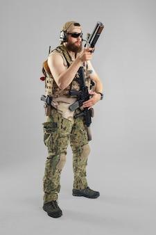 Żołnierz sił specjalnych z karabinem na białym tle.