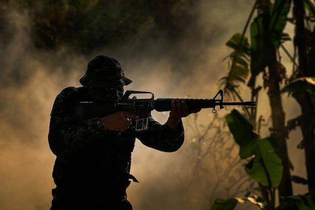 Żołnierz sił specjalnych z karabinem, oświetlenie low-key.