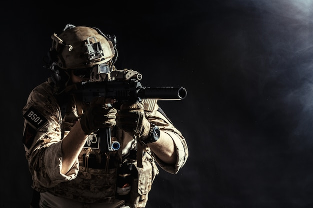 Żołnierz sił specjalnych z karabinem w ciemności