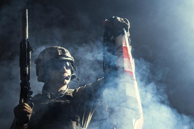 Żołnierz trzyma karabin maszynowy z flagą narodową