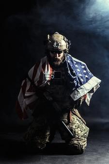 Żołnierz trzyma karabin maszynowy z flagi narodowej