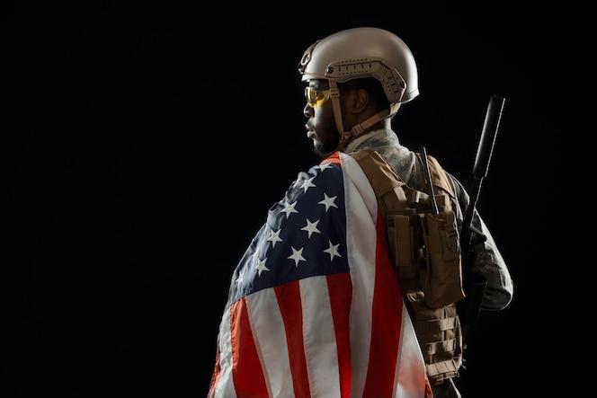 Żołnierz trzyma nowoczesną broń i amerykańską flagę na ramieniu.