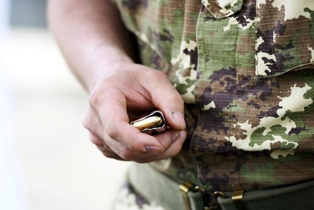 Żołnierz trzyma załadowany magazynek pistoletu