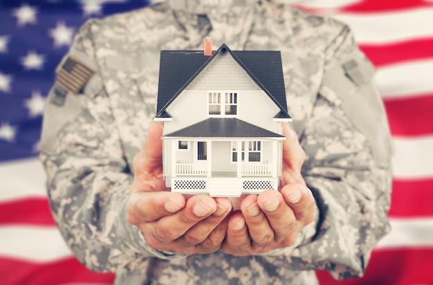 Żołnierz trzymający model domu