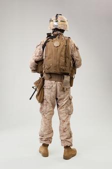 Żołnierz w amerykańskim mundurze marines z karabinem na jasnoszarym, studio strzał