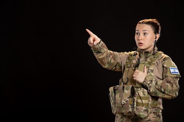Żołnierz w kamuflażu na czarnej ścianie