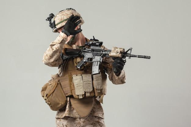 Żołnierz w kamuflażu trzyma karabin