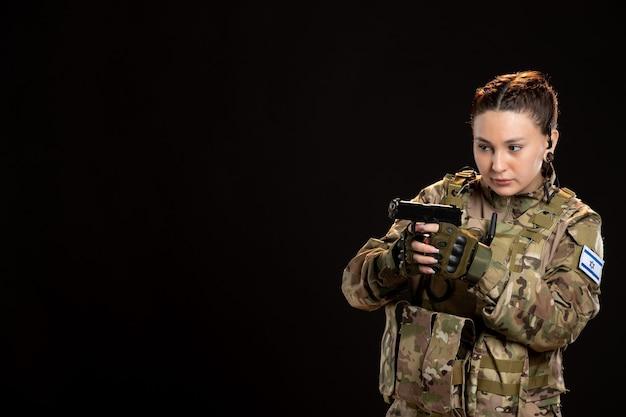 Żołnierz w kamuflażu trzymający pistolet na czarnej ścianie