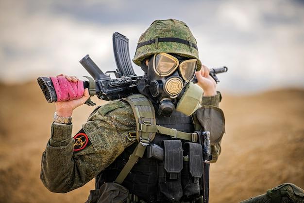 Żołnierz w masce gazowej z bronią stoi na środku pustyni