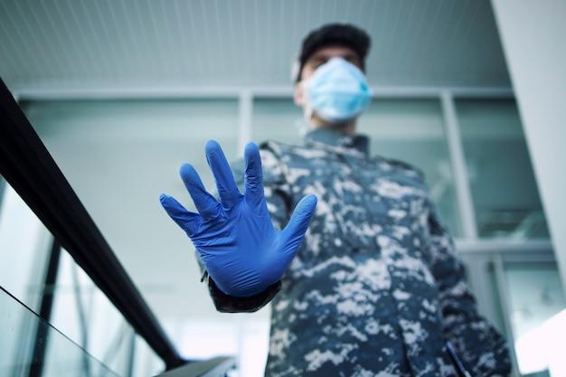 Żołnierz w mundurze kamuflażu w rękawicach ochronnych i masce ze znakiem stopu przy wejściu do szpitala