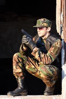 Żołnierz w mundurze ma broń.