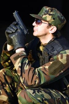 Żołnierz w mundurze trzyma pistolet.