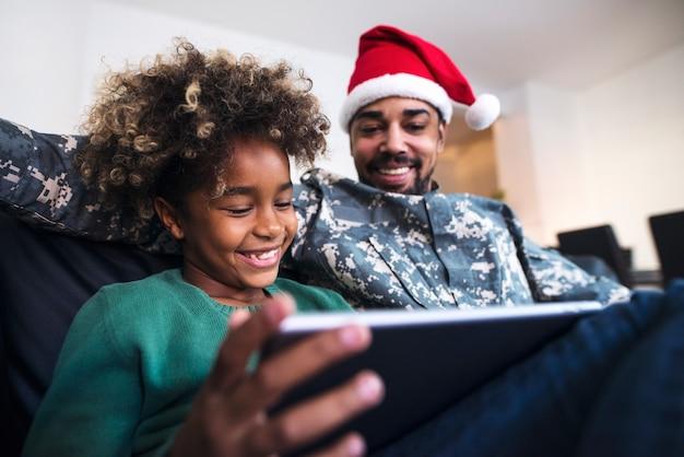 Żołnierz w mundurze w kapeluszu świętego mikołaja, siedząc obok córki na kanapie i przy użyciu komputera typu tablet