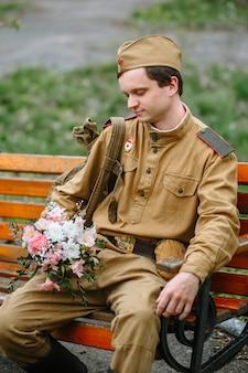 Żołnierz w sowieckim mundurze wojskowym siedzi na ławce. w jego rękach bukiet
