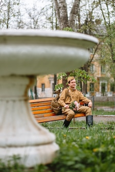 Żołnierz w sowieckim mundurze wojskowym siedzi na ławce