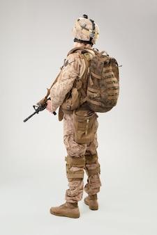Żołnierz w usa żołnierza piechoty morskiej mundurze z karabinem na jasnopopielatym tle, studio strzał