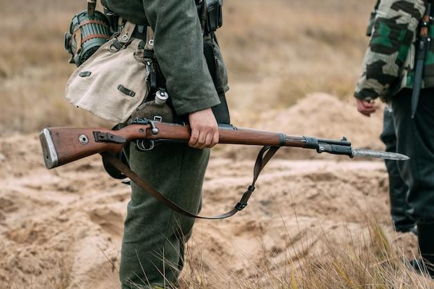 Żołnierz wehrmachtu z karabinem na pełnym biegu