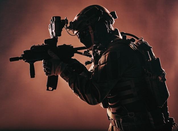 Żołnierz wojskowy, bojownik oddziału kontrterrorystycznego, najemnik firmy wojskowej w amunicji i zbroi, hełm z noktowizorem, celowanie z karabinu serwisowego z krótką lufą, niski klucz, strzelanie studyjne