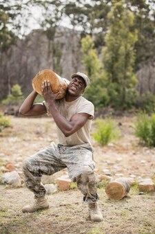 Żołnierz wojskowy niosący kłodę drzewa podczas toru przeszkód w obozie treningowym