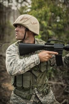 Żołnierz wojskowy podczas treningu z bronią na obozie treningowym