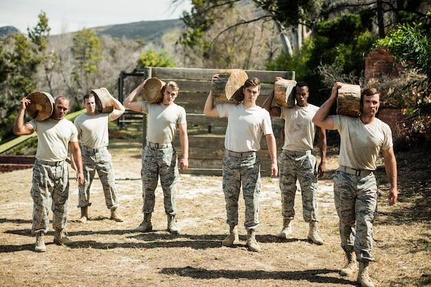 Żołnierze niosący kłodę drzewa