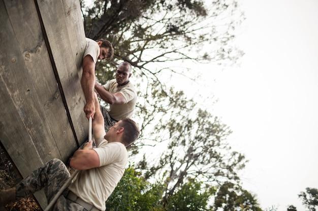 Żołnierze pomagają człowiekowi wspiąć się na drewnianą ścianę