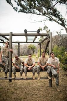 Żołnierze siedzący na torze przeszkód w obozie treningowym