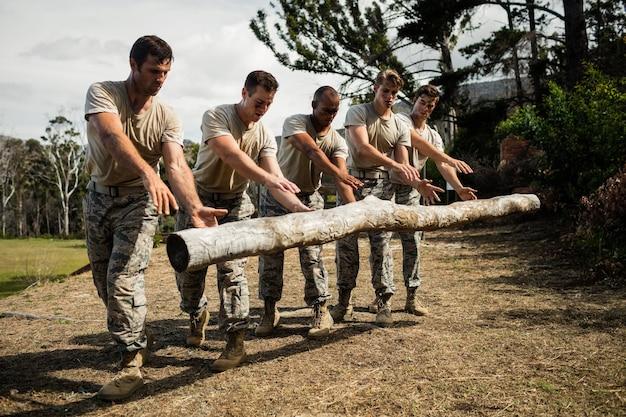 Żołnierze upuszczają kłodę drzewa