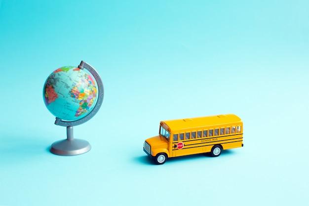 Żółta autobus szkolny zabawka blisko kula ziemska na błękit ścianie.