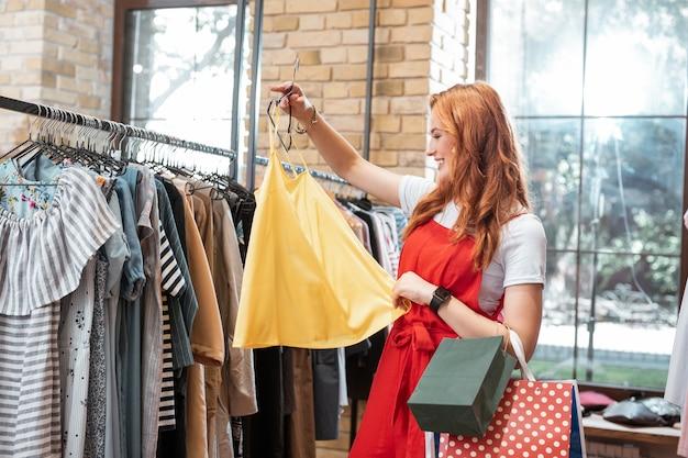 Żółta bluzka. wesoła, ładna młoda dziewczyna, ciesząc się na zakupy i uśmiechając się, patrząc na ładną żółtą bluzkę