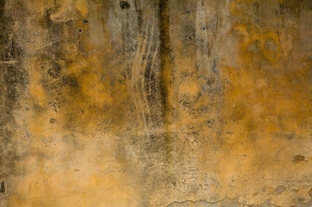 Żółta brudna sztukateria lub otynkowana ściana z pęknięciami. z bliska strzał. grunge abstrakcjonistyczna tekstura lub tło. koncepcja retro