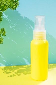 Żółta butelka kosmetyku na tych samych kolorowych polach. na boku są świeże zioła. stylowa koncepcja esencji organicznych, naturalnych produktów kosmetycznych i zdrowotnych.