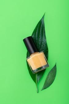 Żółta butelka lakieru do paznokci na zielonej powierzchni.