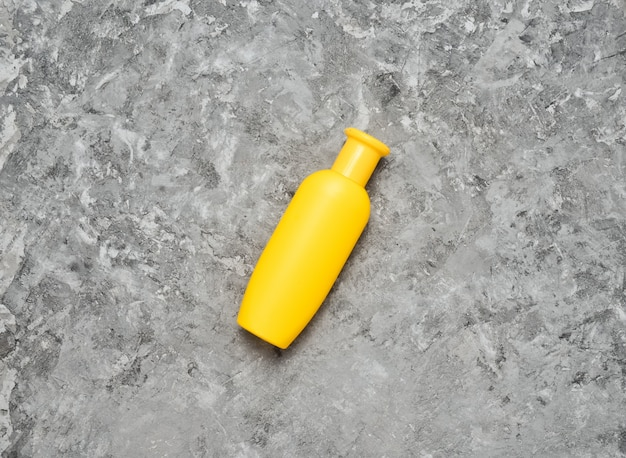 Żółta butelka szamponu na szarym betonowym stole. trend minimalizmu. widok z góry. produkty pod prysznic. miejsce na tekst.