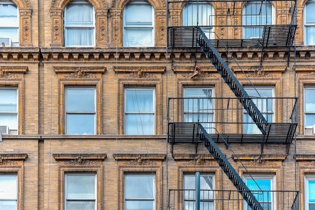 Żółta ceglana fasada i para butów wisząca na schodach przeciwpożarowych. chelsea, nowy jork.