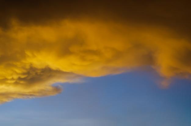 Żółta chmura od słońca wieczorem z błękitnym niebem, gdy zaczyna padać w porze monsunowej