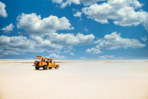 Żółta ciężarówka jedzie po piaszczystej ziemi pod zachmurzonym błękitnym niebem