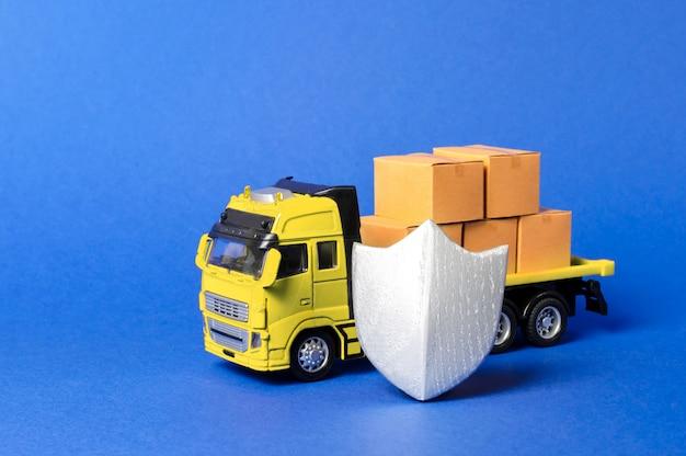 Żółta ciężarówka z kartonowymi pudełkami przykryta tarczą. ubezpieczenie ładunku, bezpieczeństwo transportu