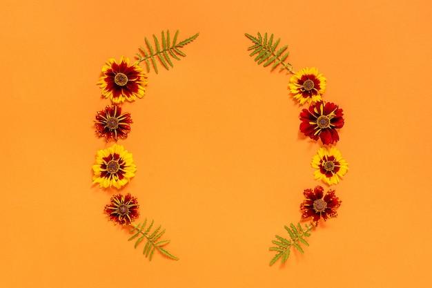 Żółta czerwona kwiat rama na pomarańczowym tle