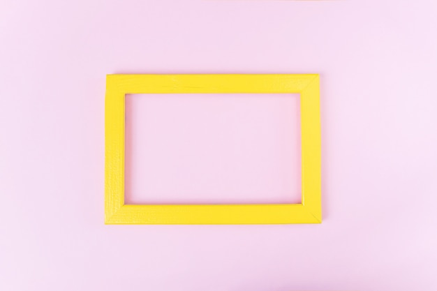 Żółta drewniana pusta ramka na różowo