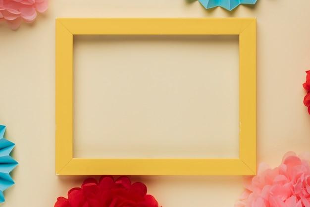 Żółta drewniana rabatowa obrazek rama z dekorującymi origami kwiatami