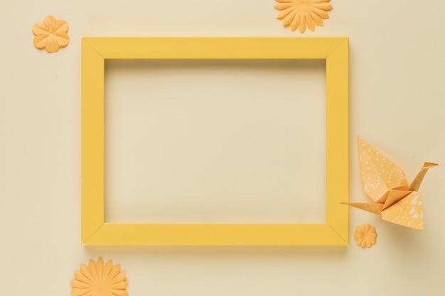 Żółta drewniana rama z papierowym ptakiem i kwiat wycinanką