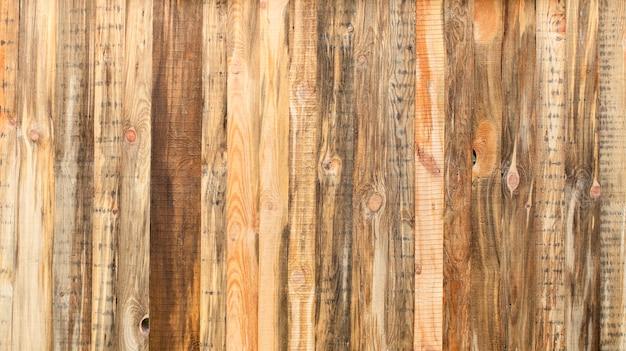 Żółta drewniana ściana ze starych desek, tekstura naturalnych materiałów.