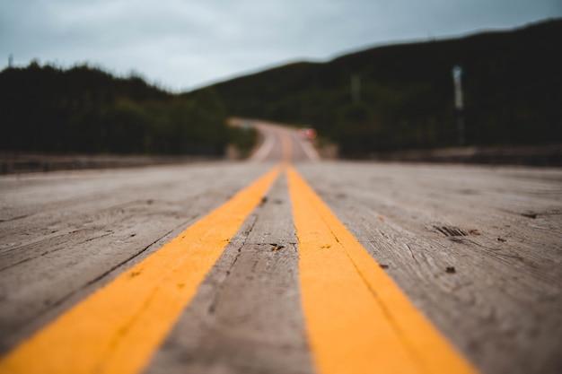 Żółta drogi linia na drewnianej podłoga