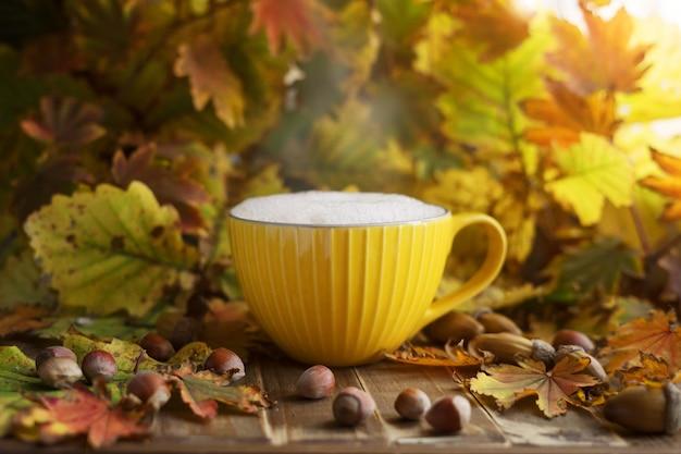 Żółta filiżanka cappuccino w jesiennych liściach z żołędziami i orzechami. jesienny klimat.